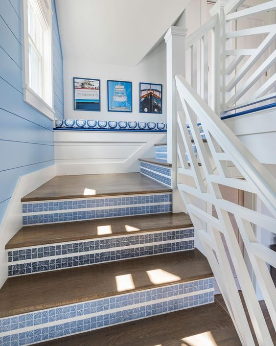 a pretty seaside staircase with stained steps and blue striped risers is a chic idea for a coastal home
