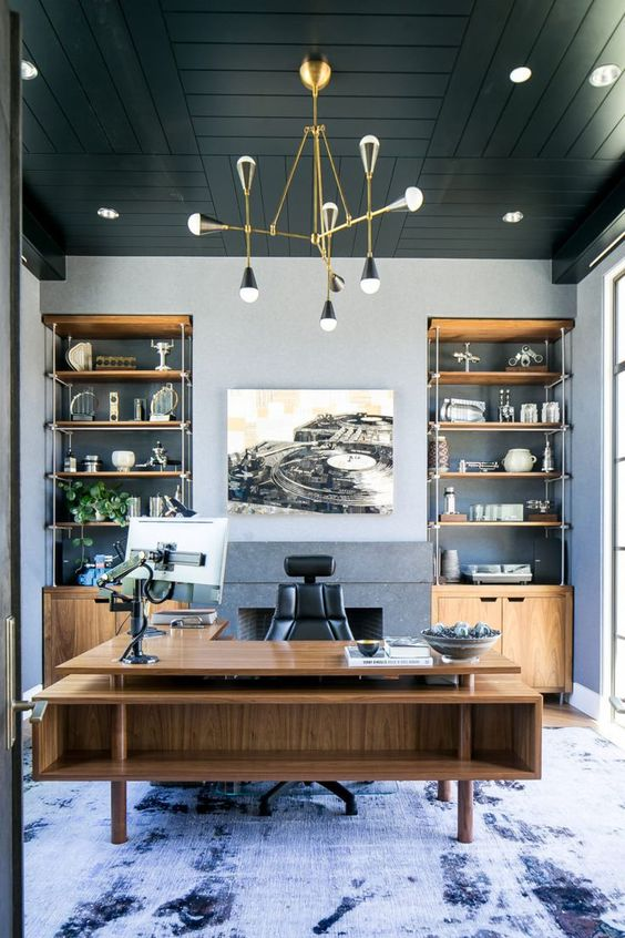 a refined beach home office with grey walls, a black wooden ceiling, built-in storage units and a large stained desk plus a sea-inspired rug