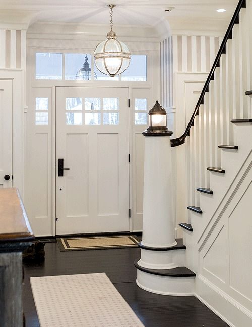 a seaside staircase in black and white, with black railing and a beacon-liek lamp on the post is a cool and bold idea
