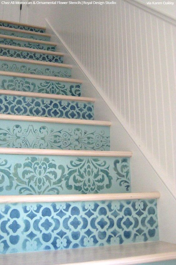 a seaside staircase with risers paitned light blue and stenciled with various patterns in navy shades
