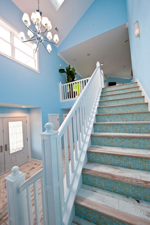 a seaside staircase with tiled steps and blue mosaic tile risers feels Mediterranean and looks beautiful