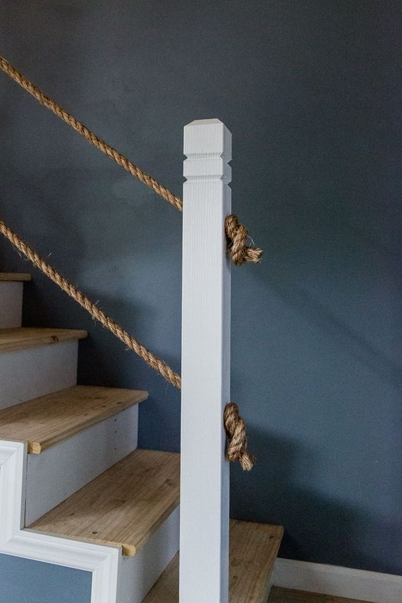 a simple and casual staircase with stained steps and rope railing is a cool and chic idea to rock