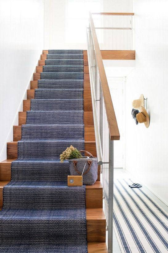a stained staircase covered with navy carpet feels seaside and coastal-like thanks to just this textile piece