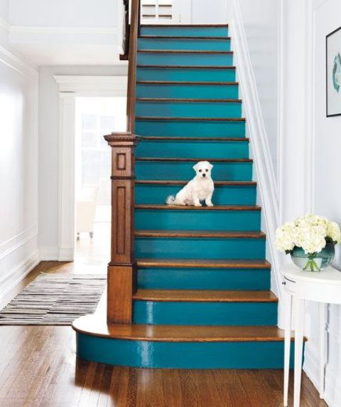 a statement coastal staircase with stained steps and teal risers is a lovely idea for a vintage coastal home