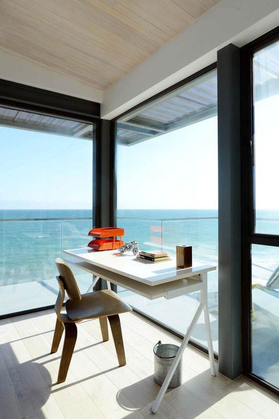 a stunning modern beach home office with glass walls, a sleek white desk and a stained chair and gorgeous sea views