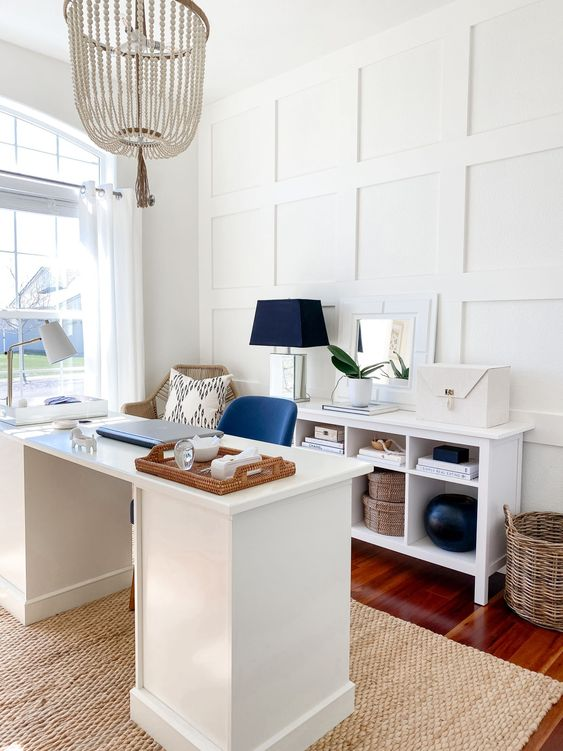 a stylish beach home office with white paneling, white furniture, navy accents, baskets and a wooden bead chandelier is gorgeous