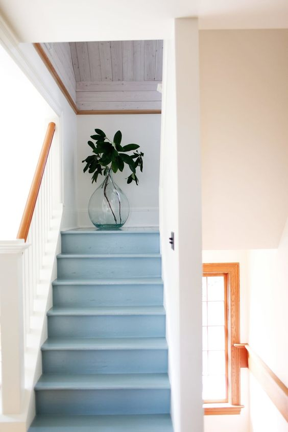 a subtle light blue staircase with white railing feels seaside, coastal or beach-like and will fit any of such houses