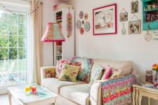 a summer living room with a bold gallery wall, printed pillows and a blanket, a bright lamp and chandelier