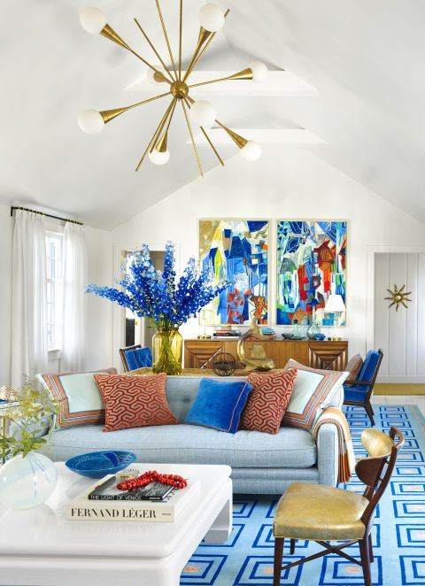a super bold living space with bright artworks, blooms, a blue printed rug, printed pillows is a fun and bold summer space