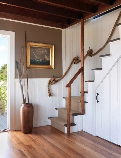 a very simple coastal staircase with a neutral carpet and rope railing is a stylish solution for a realxed beach house
