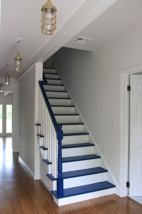 a very simple nautical staircase in navy and white is a bold and contrasting solution to rock in your seaside home