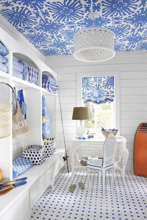a vintage beach home office with a large white storage unit, a blue wallpaper ceiling, a tiled floor and a white desk and a chair