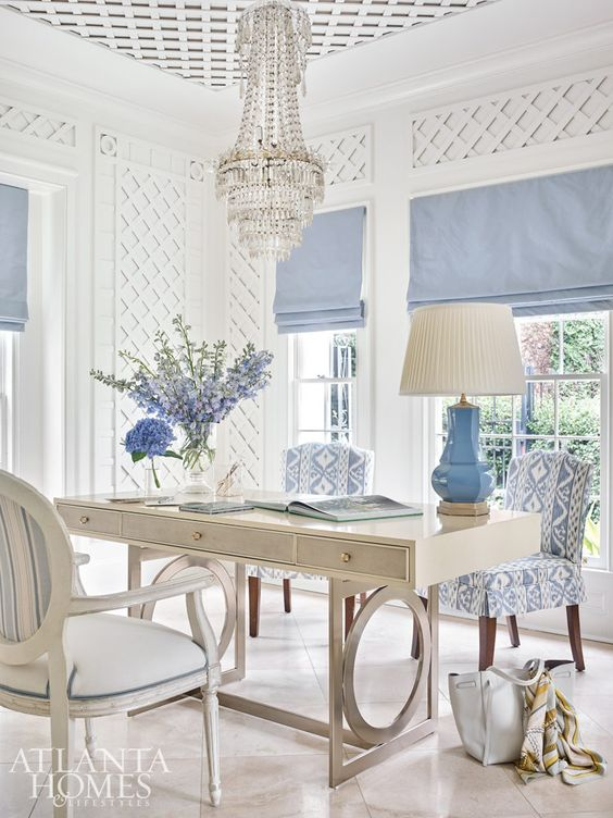 a vintage coastal home office with paneling on the walls, a neutral desk, chic printed chairs, a crystal chandelier and blue curtains