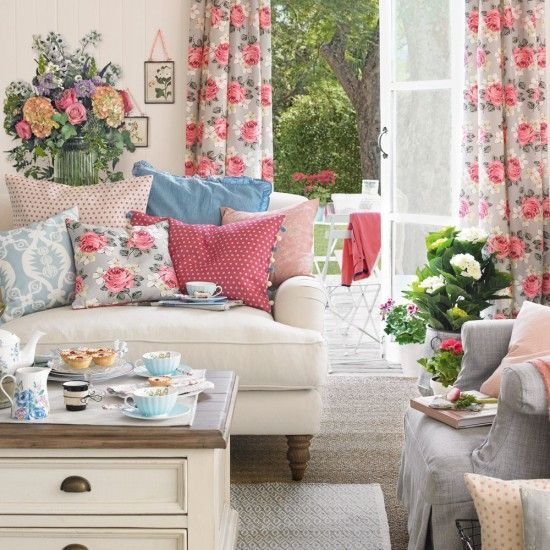 a vintage-inspired living room with florla curtains, printed pillows, potted blooms and greenery and bright blankets for summer