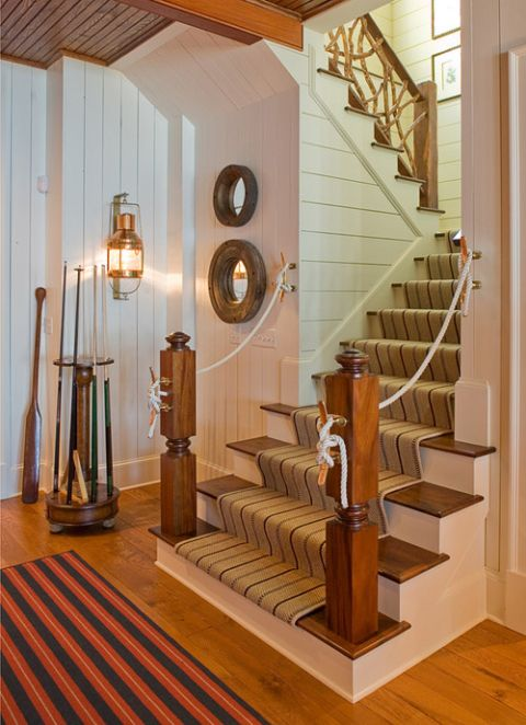 a vintage seaside staircase with stained steps, with a striped carpet and rope railing is a chic nautical idea