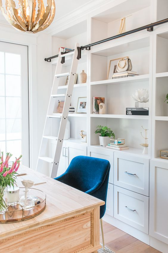 a white coastal home office with a large storage unit with a ladder, a light-stained desk and a navy chair plus a catchy chandelier