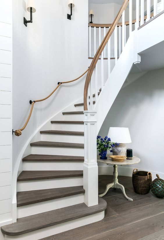 an elegant rounded staircase with rope railing and wooden railing looks very chic and stylish