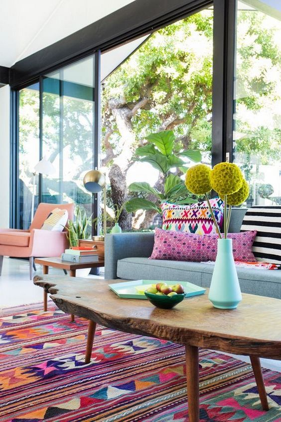 bright yellow blooms, printed colorful pillows, a bright boho rug make the living room feel like summer