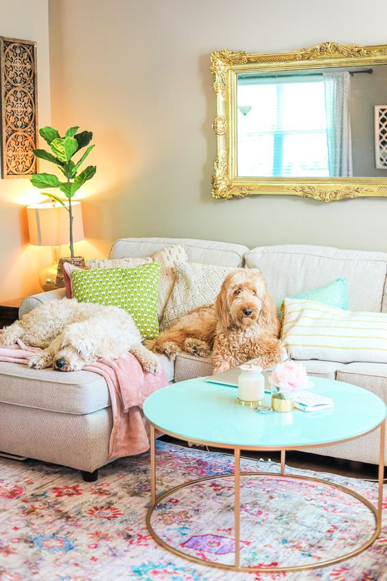 pastel pillows and blankets, a floral print rug, a turquoise table and pillows for a fun and bold living room