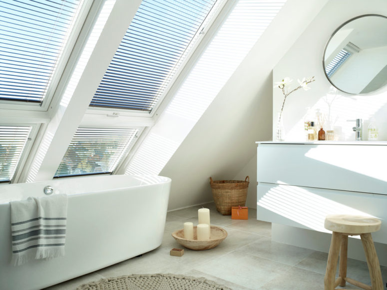 a contemporary attic bathroom with large windows, an oval bathtub, a vanity with a round mirror, a wooden stool  (VELUX)