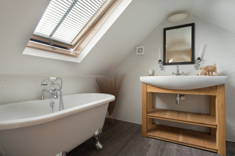 a modern attic bathroom with a wooden vanity, a clawfoot bathtub, a sink and a blinded window  (Colin Cadle Photography)