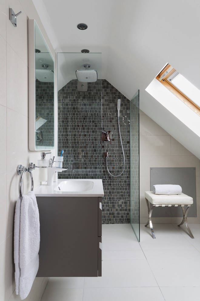 a contemporary attic bathroom with a grey tile wall in the shower, a grey floating vanity and a small stool  (Ripples Bournemouth)