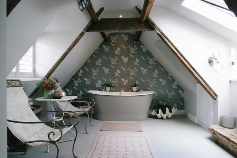 an elegant attic bathroom with a wallpaper statement wall, a grey bathtub, elegant chairs and potted blooms  (Aston Matthews)