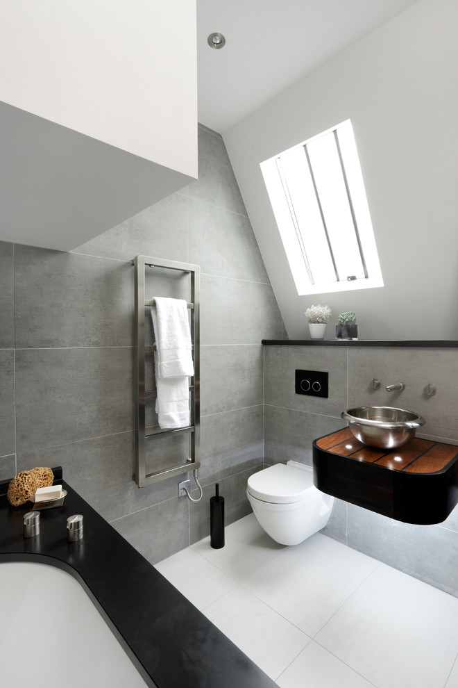 a bold attic bathroom with grey tiles, a black small vanity, a black clad tub and a white floor  (CUBIC Studios Limited)
