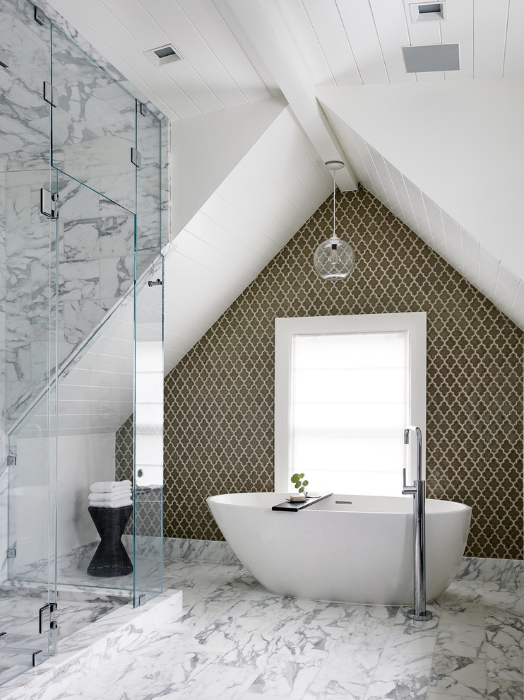 an elegant attic bathroom with marble tiles, an oval tub, a catchy tile statement wall  (Art of Construction Inc)