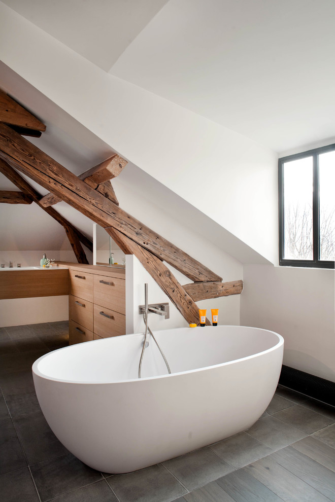 a contemporary meets rustic bathroom with wooden beams, an oval tub and white cabinets  (Olivier Chabaud Architecte)