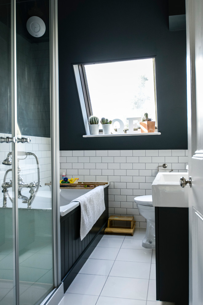 a small elegant attic bathroom with white subway tiles, a black clad bathtub and vanity, a white tub and sink  (Lauren Bryan Knight)