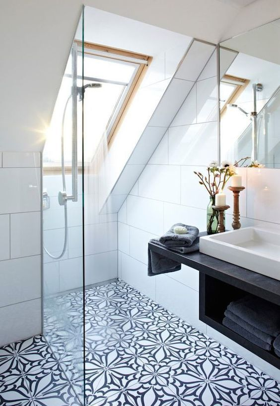 a black and white attic bathroom with mosaic tiles, a shower space with skylights, a floating vanity