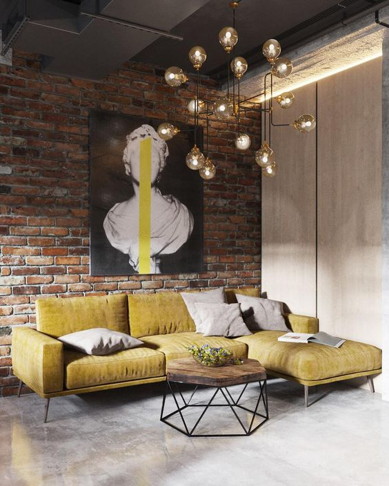 a brick wall, a metal ceiling, a concrete floor makes up a cool base for an industrial living room, and a bulb chandelier adds to it