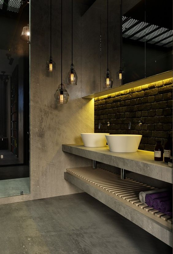 a catchy industrial bathroom of concrete, with a black brick backsplash, a concrete vanity and a cluster of pendant lamps
