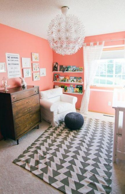 a cheerful grey and coral nursery with coral walls, a printed rug, a stained sideboard, a cool chandelier and whiet touches