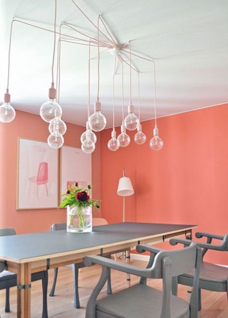 a chic contemporary dining room with a bulb chandelier, a grey dining table and chairs and bright artworks
