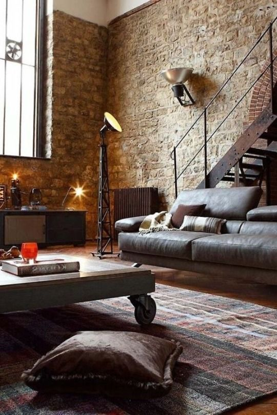 a chic living room with a leather sofa, a wood and metal coffee table on casters, a metal staircase and brick walls