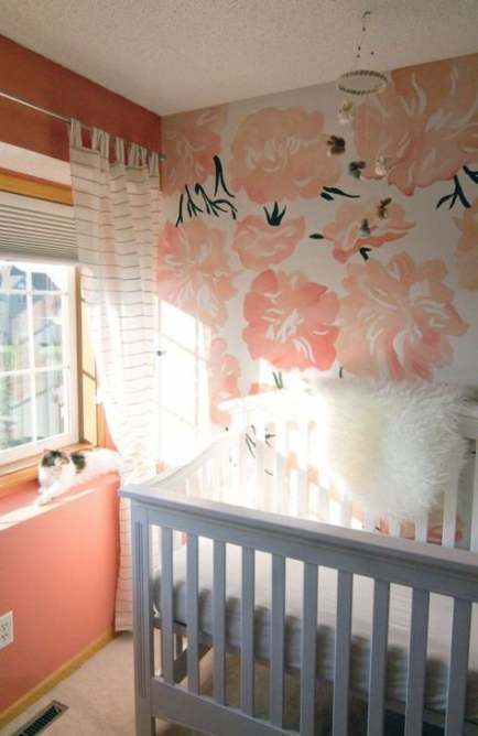 a colorful nursery with a floral statement wall, coral walls, a grey crib and white textiles to refresh the space