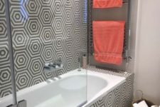 a contemporary bathroom with geometric print walls and floors, bright coral towels and a basket for storage