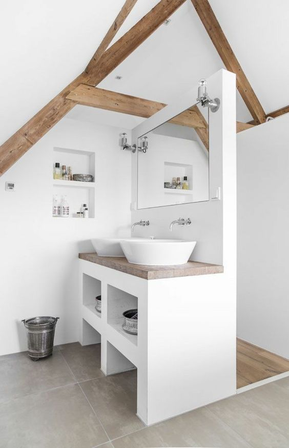 a contemporary white attic bathroom with wooden beams and countertops plus built-in storage spaces