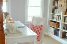 a cool home office with dove grey walls, striped textiles, elegant white furniture is a chic space to work in