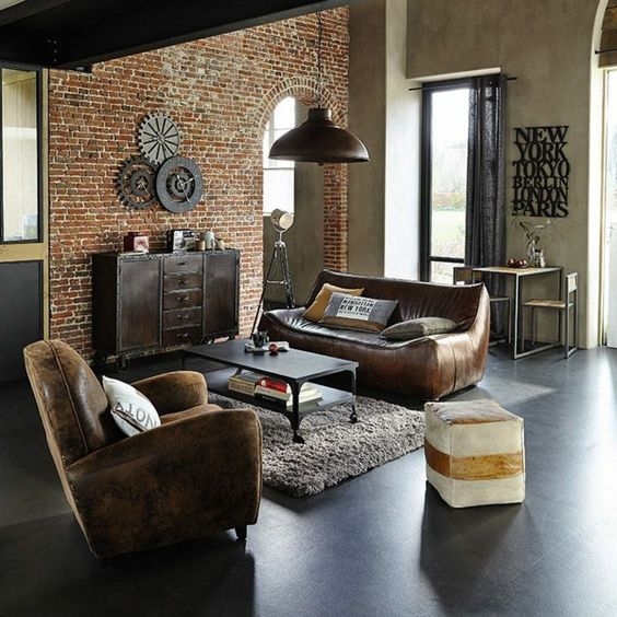 a cozy industrial space done with leather furniture, a brick statement wall, a furry rug and a metal coffee table