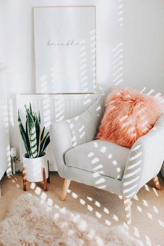 a cozy nook with a dove grey chair, a fluffy coral pillow and a faux fur rug is a cute and fun idea for a contemporary home