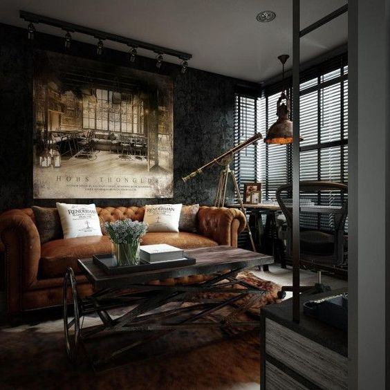 a dark industrial room with a leather sofa, a wood and metal table, a vintage metal pendant lamp and a fur rug