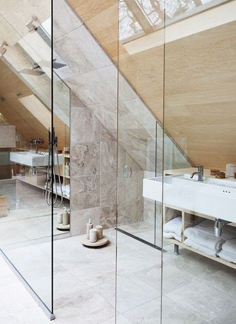 a marble tile and wood attic bathroom with a shower space, many candles and skylights