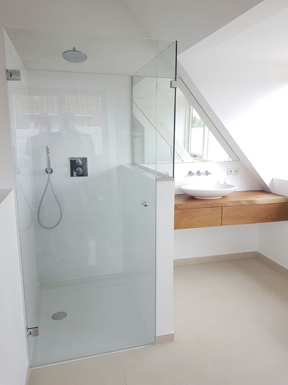 a minimalist attic bathroom with a wooden floating vanity and a white shower