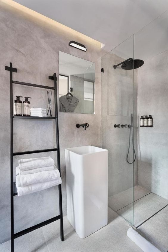 a minimalist industrial bathroom done of concrete, with built-in lights, a ladder and black fixtures