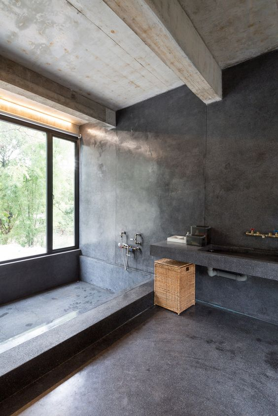 a minimalist industrial bathroom done with white concrete and black stone, a large built in tub, a vanity with a built in sink and a basket