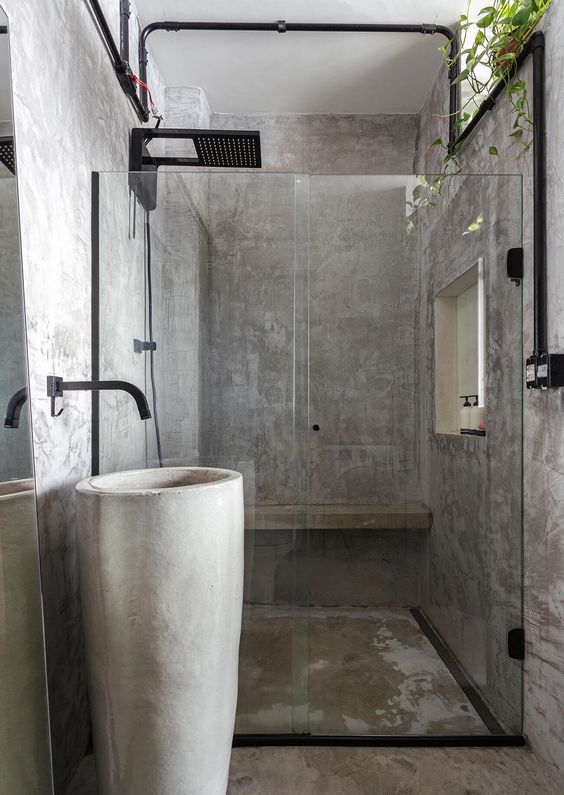 a minimalist industrial bathroom fully clad with concrete, a free-standing sink, black fixtures and potted greenery
