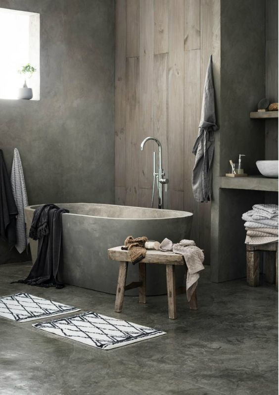 a minimalist industrial bathroom with concrete walls and a floor, a wooden wall, concrete vanities and a bathtub, wooden stools